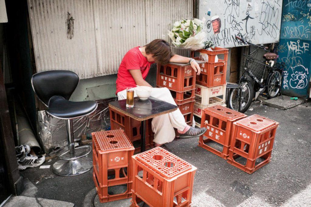 pijany japończyk opierający się o skrzynki z alkoholem