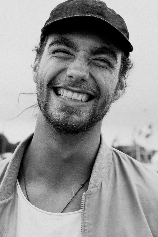 Uśmiechnięty szeroko mężczyzna w kurtce i czapce