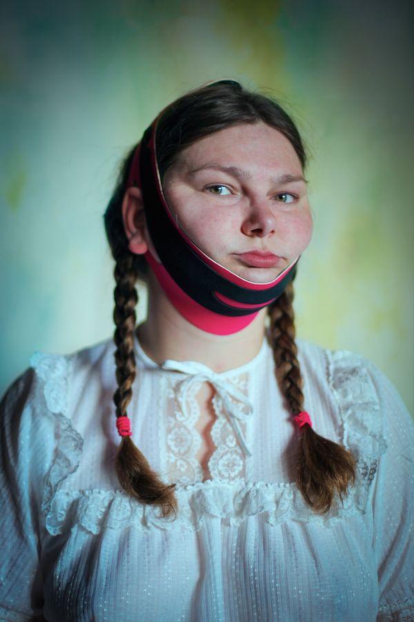Portret dziewczyny w warkoczach, białej sukience z dziwną opaską dookoła podbródka