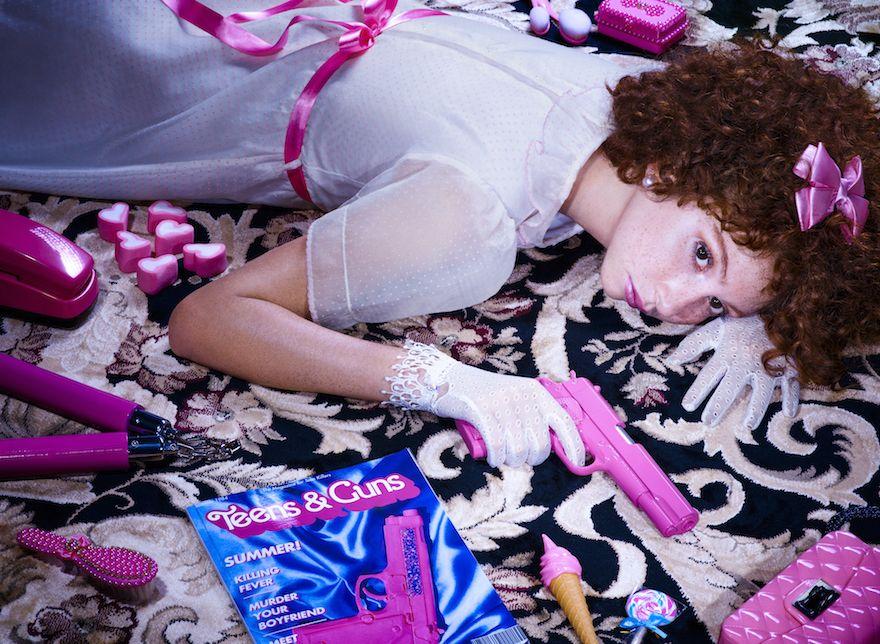 dziewczyna w białych rękawiczkach na rękach leżąca na podłodze z różowym plastikowym pistoletem