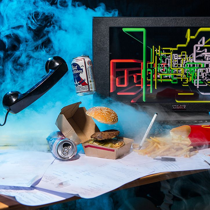 Biurko ze słuchawką do telefonu, komputerem, hamburgerem i dymem