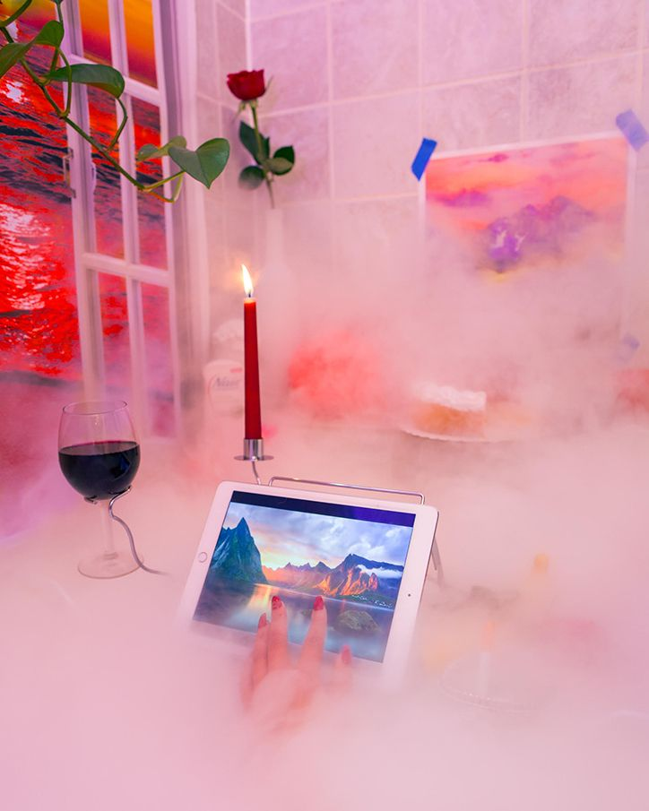 Wanna z widokiem na plażę, dymem, tabletem, świeczką i lampką wina
