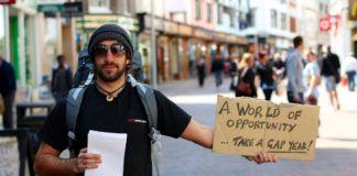 Mężczyzna z plecakiem i chustką na głowie trzymający tabliczkę z kartonu