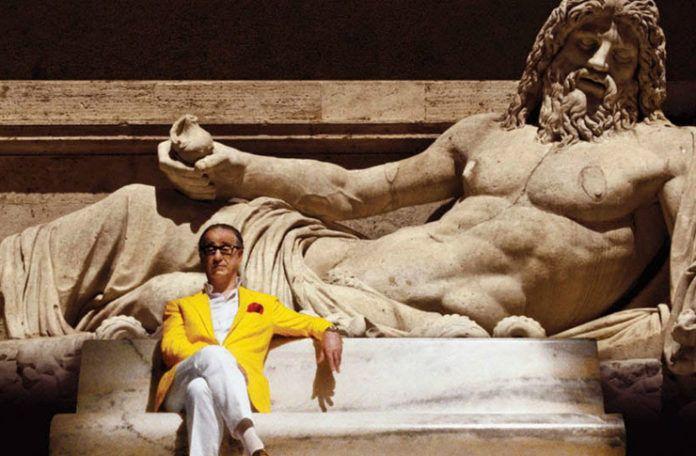 Mężczyzna w podeszłym wieku siedzi na ławce z kamienia na tle rzeźby.
