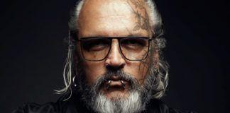 Mężczyzna z siwymi włosami i brodą, w prostokątnych okularach z kolczykami w dolnej wardze