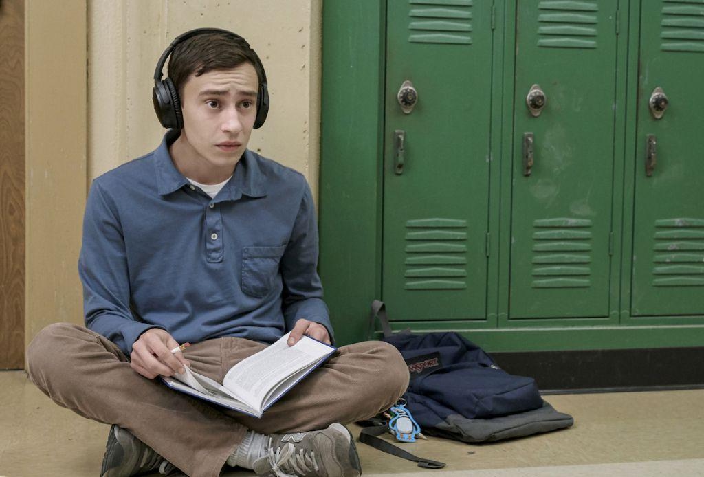 Chłopiec w słuchawkach siedzi na podłodze na korytarzu szkolnym, trzymając w rękach książkę.