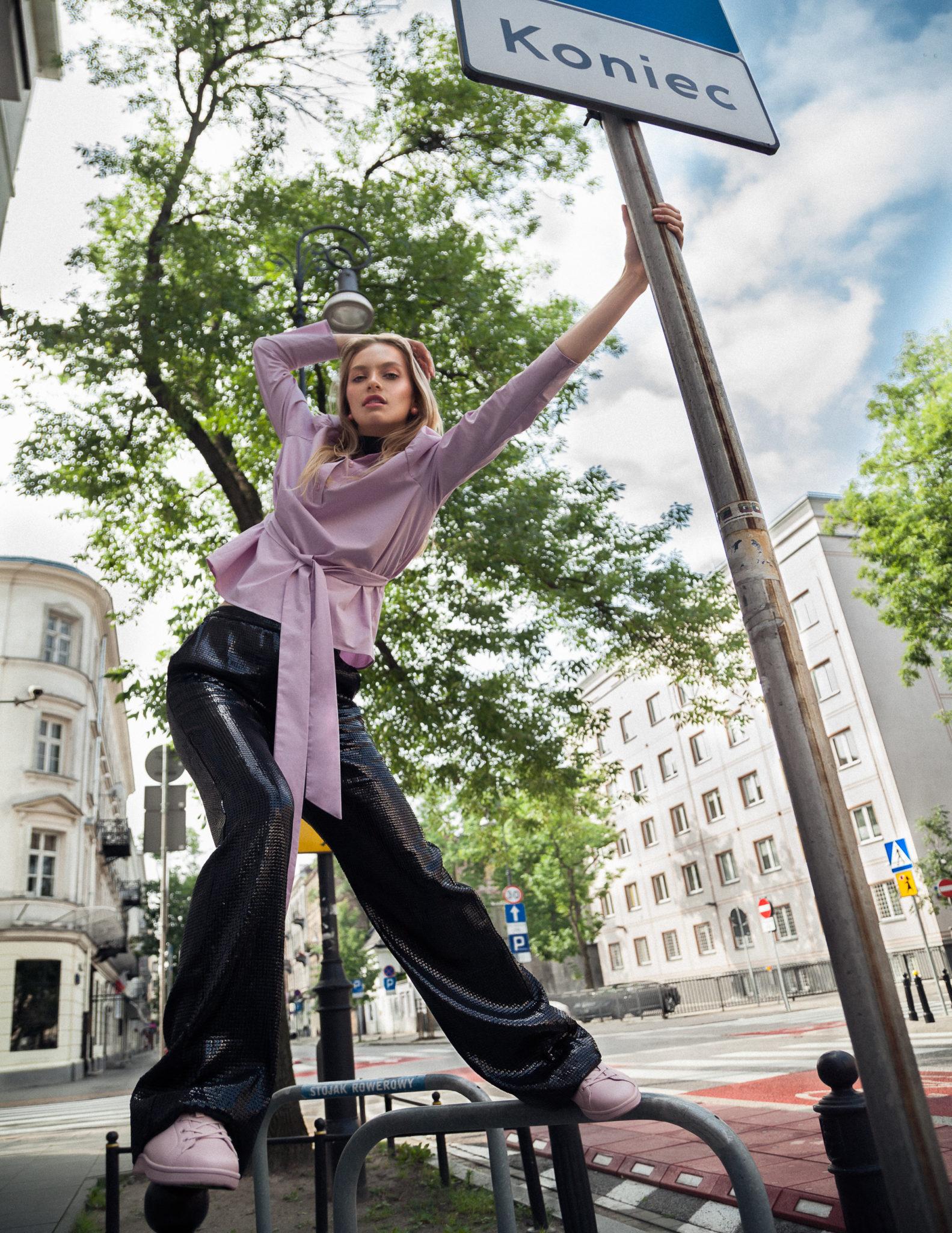 Dziewczyna w czarnych spodniach i fioletowej bluzce trzymająca się za słup na ulicy