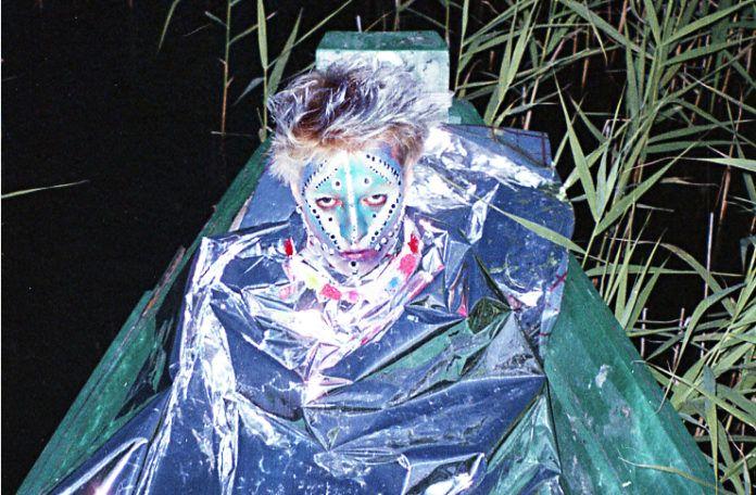 Młody mężczyzna cały pomalowany na twarzy siedzi w folii aluminiowej na łódce pośród trzcin.