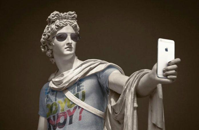 Klasyczna rzeźba ubrana w koszulkę, szalik, okulary, trzymająca w ręku iPhone'a
