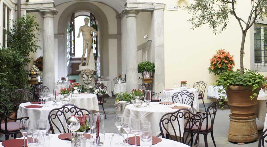Wnętrze włoskiej restauracji. Stoliki z białymi obrusami ustawione na dziedzińcu.