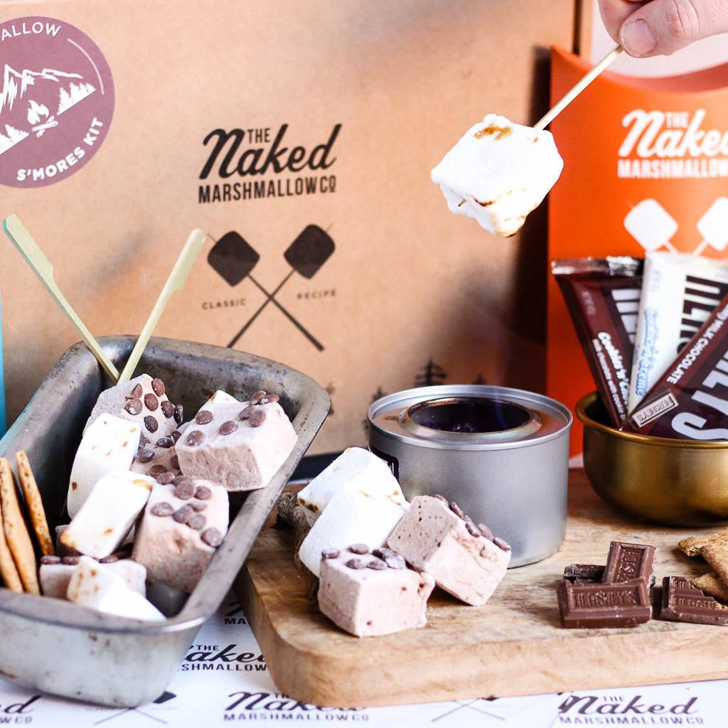 Pianki z czekoladą na tle pudełka firmy The Naked Marshmallow.