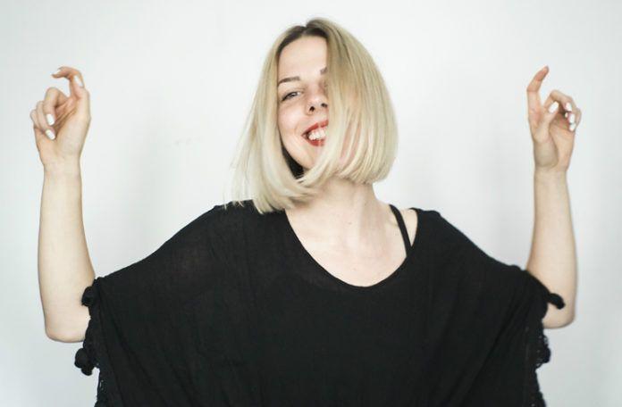 Blondwłosa dziewczyna ubrana w czarną bluzkę tańcząca na tle białej ściany