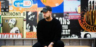 Mężczyzna ubrany na czarno, na tle kolorowej, obklejonej plakatami sciany