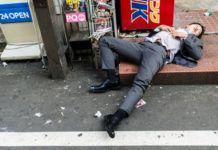 pijany japończyk śpiący okrakiem w garniturze na ulucy Tokio