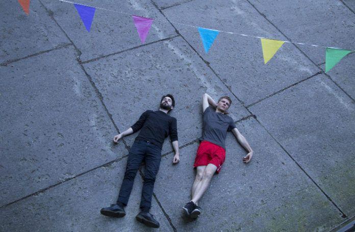 Dwóch chłopaków leżących na chodniku, nad nimi girlanda z chorągiewek