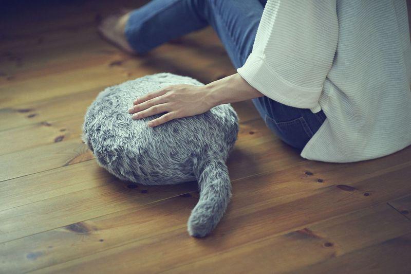 Kobieta siedząca na podłodze, trzymająca rękę na poduszcze która wygląda jak tułów kota