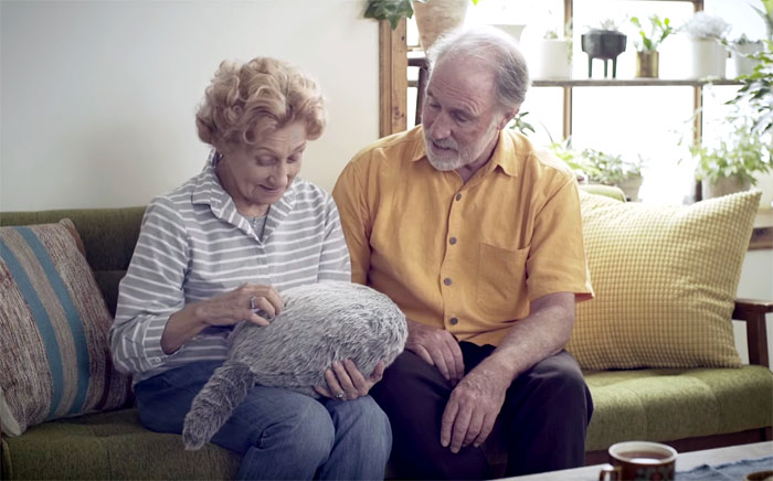 Starsza para trzymająca na kolanach poduszkę w kształcie tułowia kota
