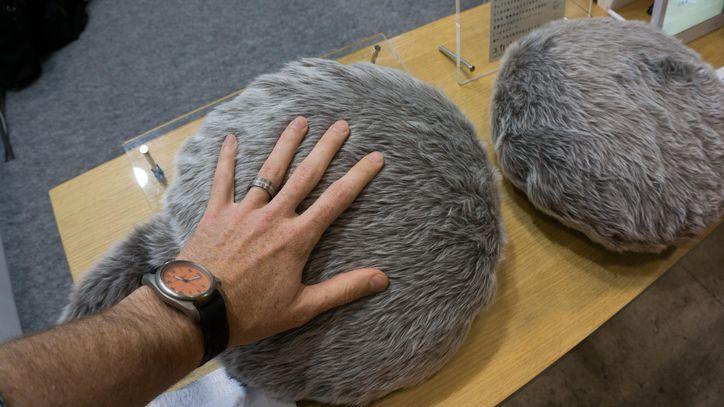 Męska dłoń położona na poduszcze wyglądającej jak tułów kota