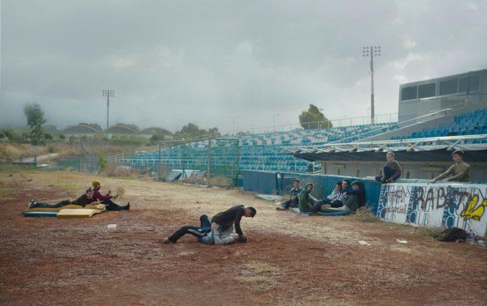 Grupka chłopców bije się na tle opuszczonego stadionu.