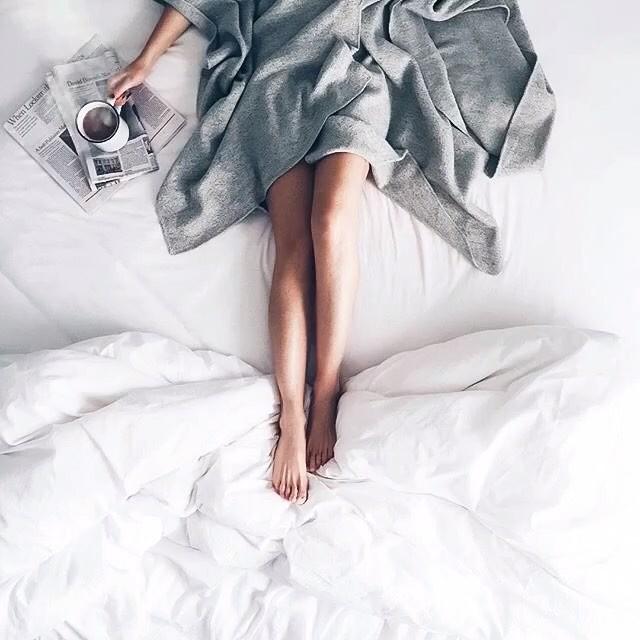 mała czarna kawa i gazeta porankiem w łóżku z dziewczyną w szlafroku i białej pościeli