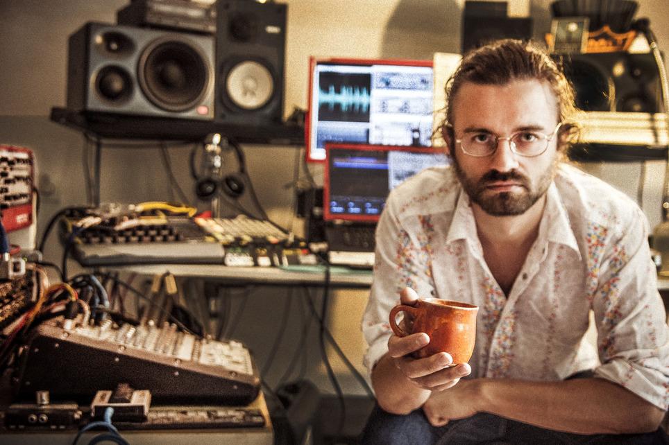 Mężczyzna z brodą siedzący i trzymający kubek w studio nagraniowym