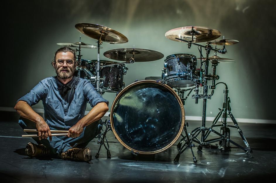 Mężczyzna w jeansie, siedzący na scenie wśród bębnów perkusji