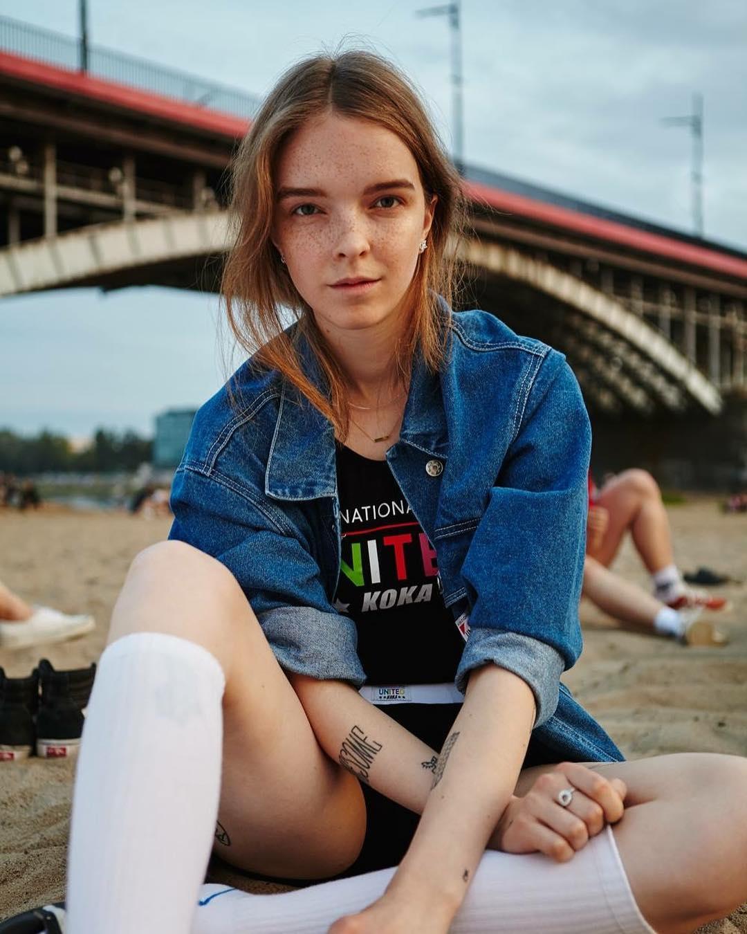 dziewczyna bez makijażu siedząca na plaży ubrana w koszulkę KOKA, kurtkę dżinsową odsłaniającą jej tatuaże i zakolanówki