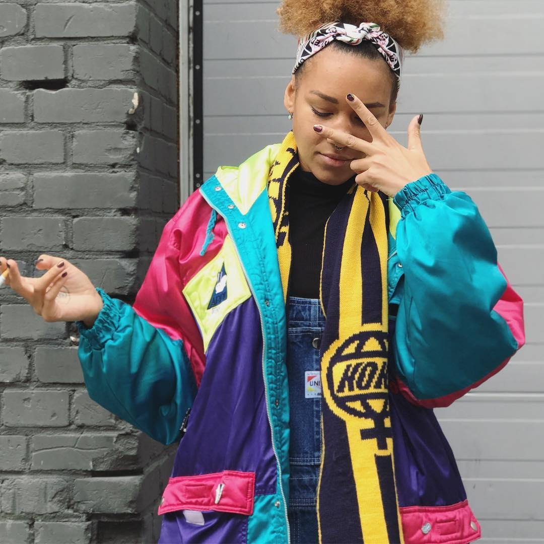 dziewczyna w kolorowym ortalionie pokazująca znak pokoju