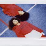 Dwie ciemnoskóre dziewczyny ubrane w czerwone bluzy leżące na boisku