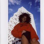 Ciemnoskóra dziewczyna na tle białego bloku, ubrana w czerwoną bluzę i czarne majtki