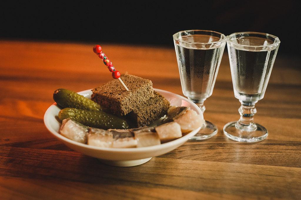 Dwa kieliszki wódki, a obok na talerzu ogórki i chleb z wbitą wykałaczką. Wszystko stoi na stole