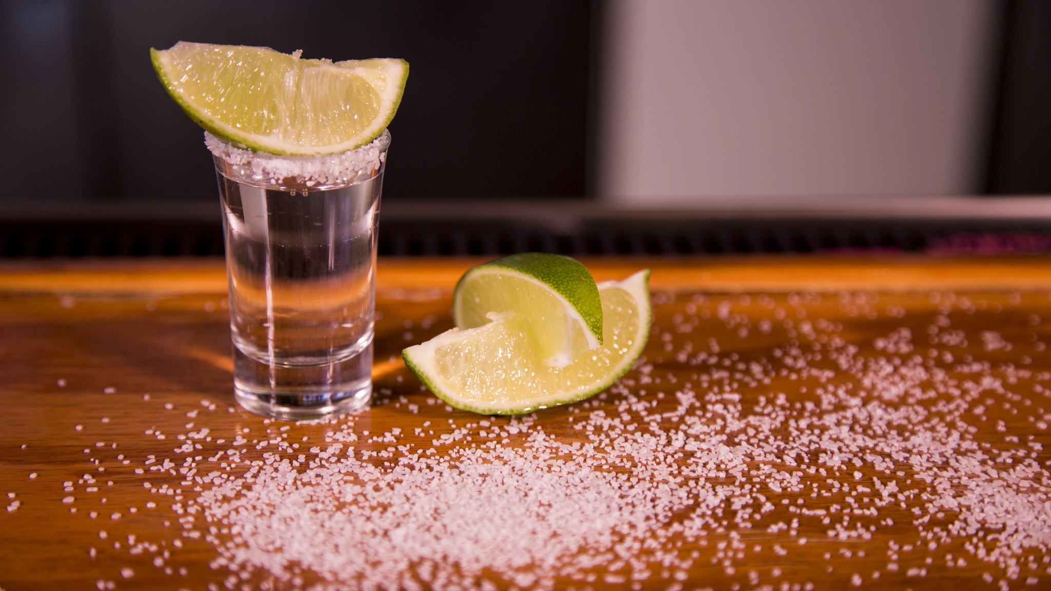 Kieliszek tequili z cząstką limonki stojący na stole, a obok kolejne limonki i rozsypana sól