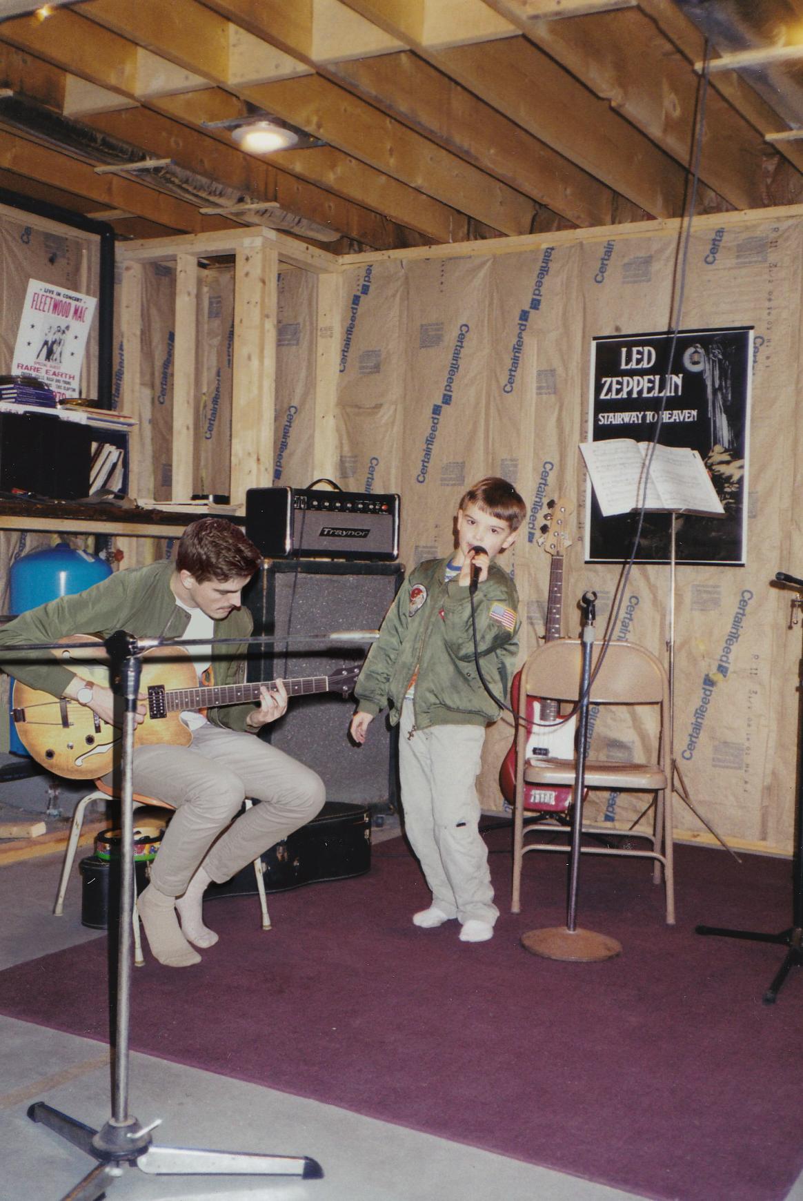 Mężczyzna gra na gitarze, chłopak śpiewa