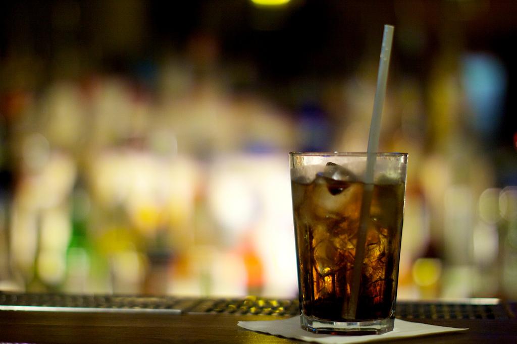 Szklanka rumu z lodem i słomką stojąca na stole