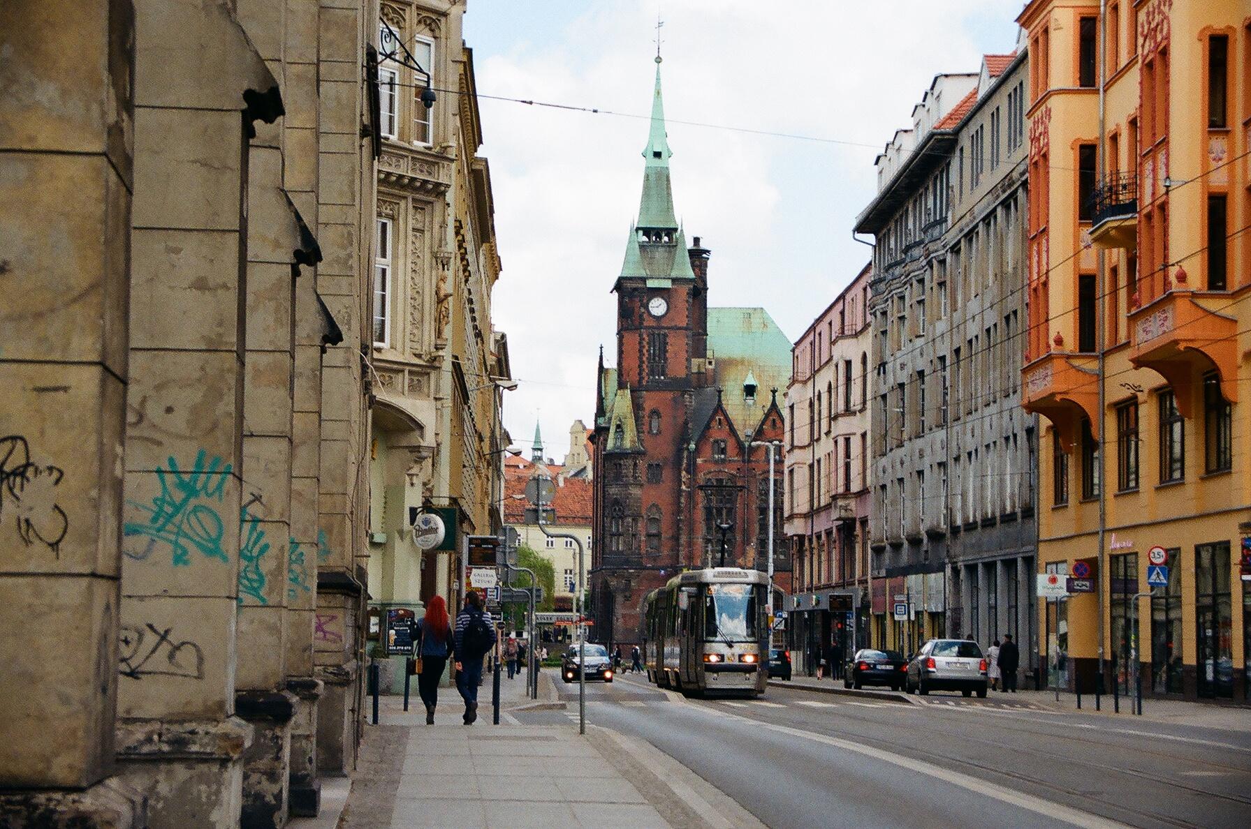 Zdjęcie ulicy, w tle jest tramawaj i para przechodniów.