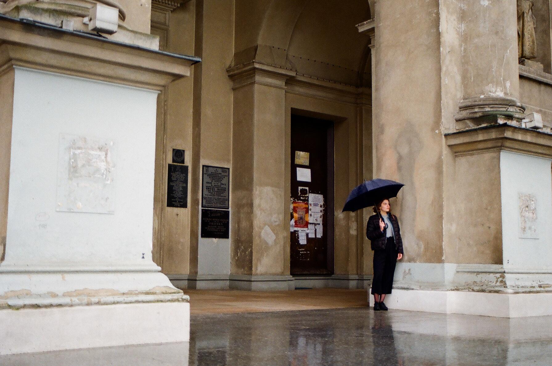 Młoda kobieta stoi na przedsionku kościoła z parasolką.