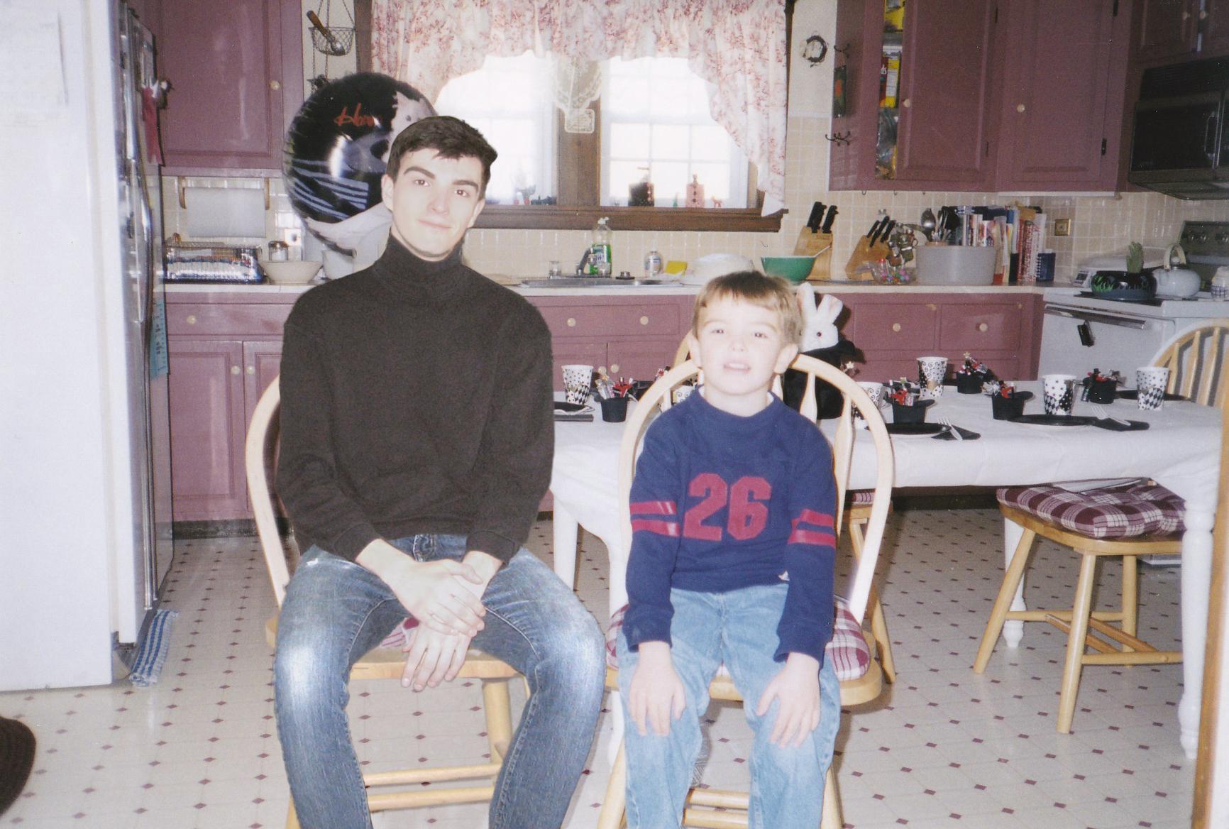 Chłopiec i mężczyzna siedzą w kuchni na krzesłach