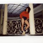 Ciemnoskóra dziewczyna pozująca na korytarzu, przy kolumnie w czerwonej bluzie i czarnych majtkach