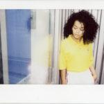 Ciemnoskóra dziewczyna w żółtej koszulce i białej spódnicy stojąca przy oknie