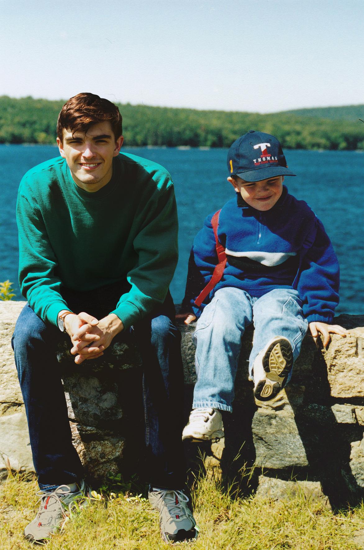 Chłopiec i mężczyzna siedzą na murku. Za nimi jezioro