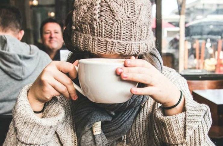 Dziewczyna zakrywająca twarz kukiem z kawą