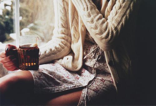 Dziewczyna siedząca na parapecie w swetrze z kupkiem w ręku