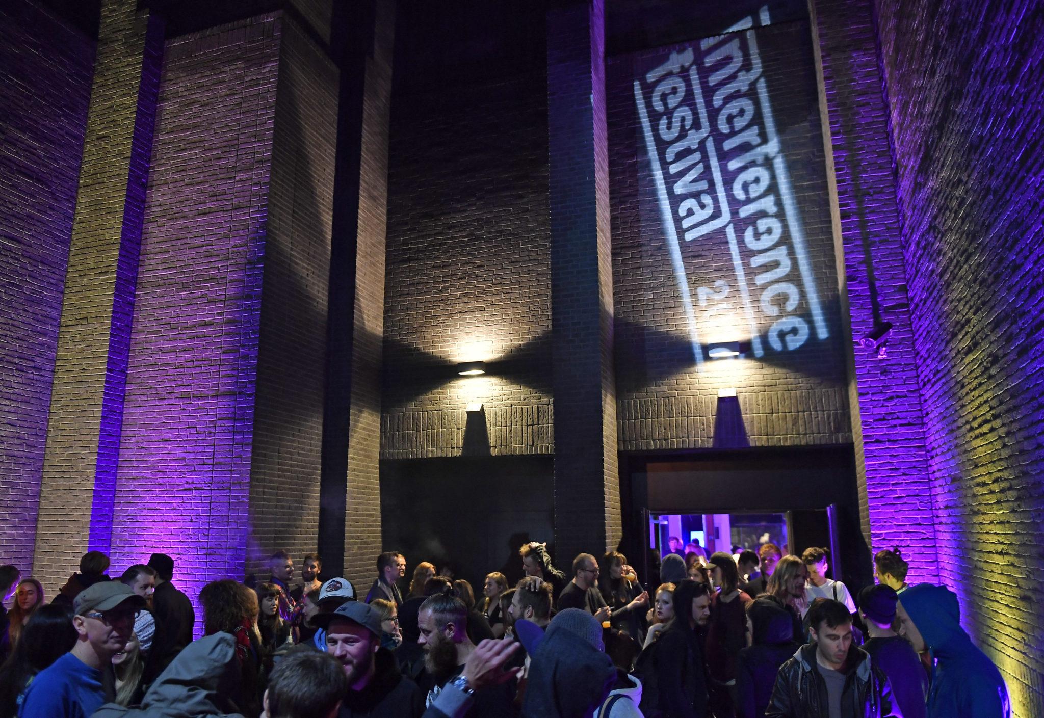 Hala wypełniona ludźmi, na ścianie napis Interference Festival