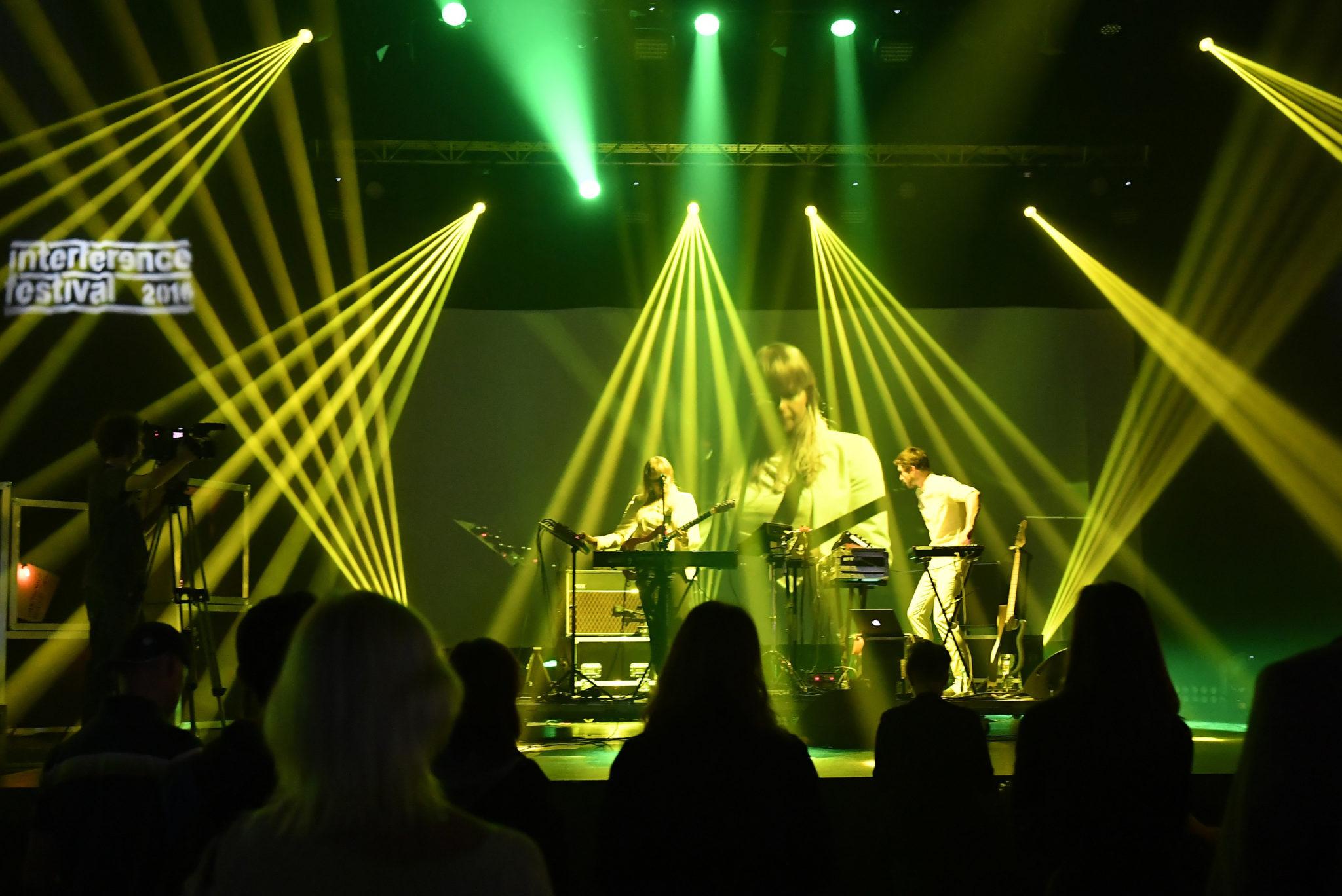 Oświetlona reflektorami scena z zespołem