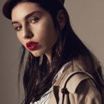Portret ciemnowłosej dzewczyny w czapce i z czerwoną szminką