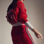 Dziewczyna ubrana w czerwony dres z czerwonym plecakiem na plecach i okularach na nosie