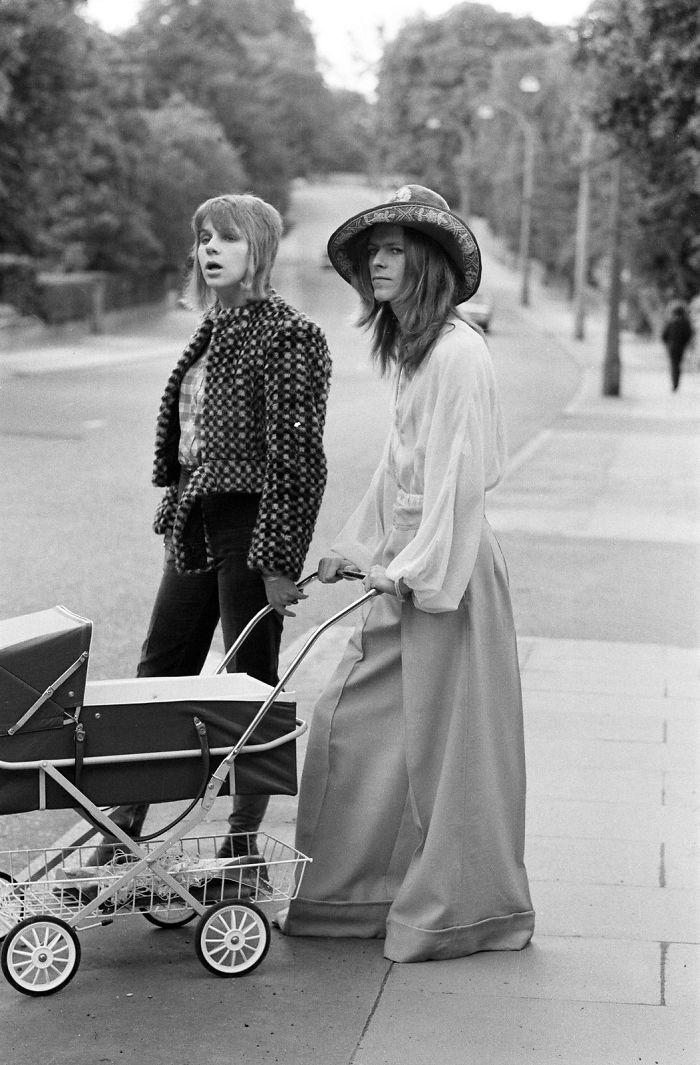 Czarno-białe zdjęcie przedstawiające kobietę i mężczyznę na spacerze z wózkiem