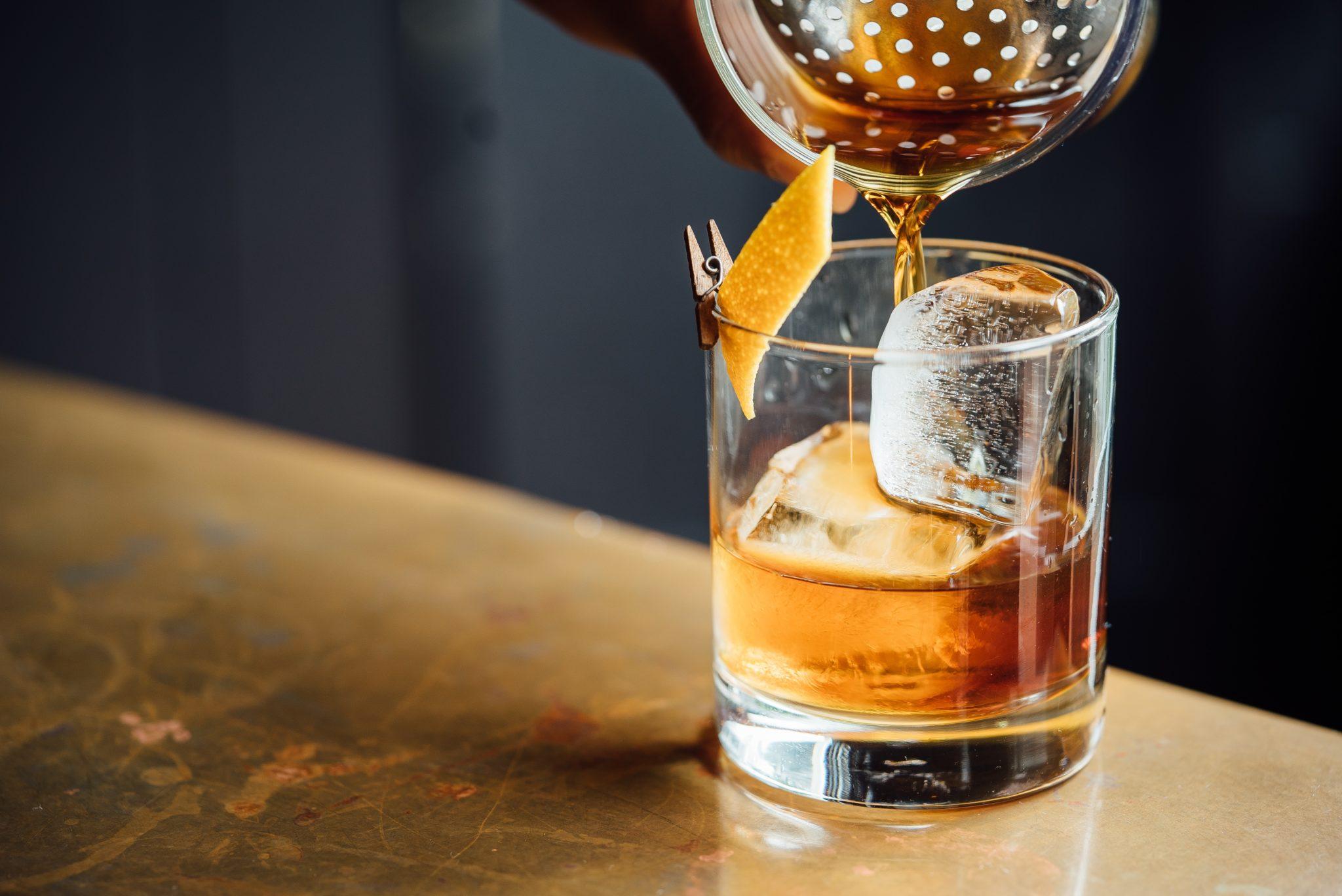 Szklanka whisky z lodem, do któej nalewany jest alkohol