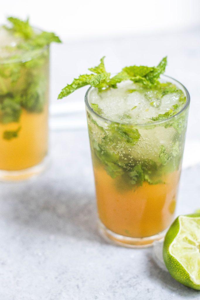 Dwie szklanki z pomarańćzowymi drinkami, udekorowane listkami mięty