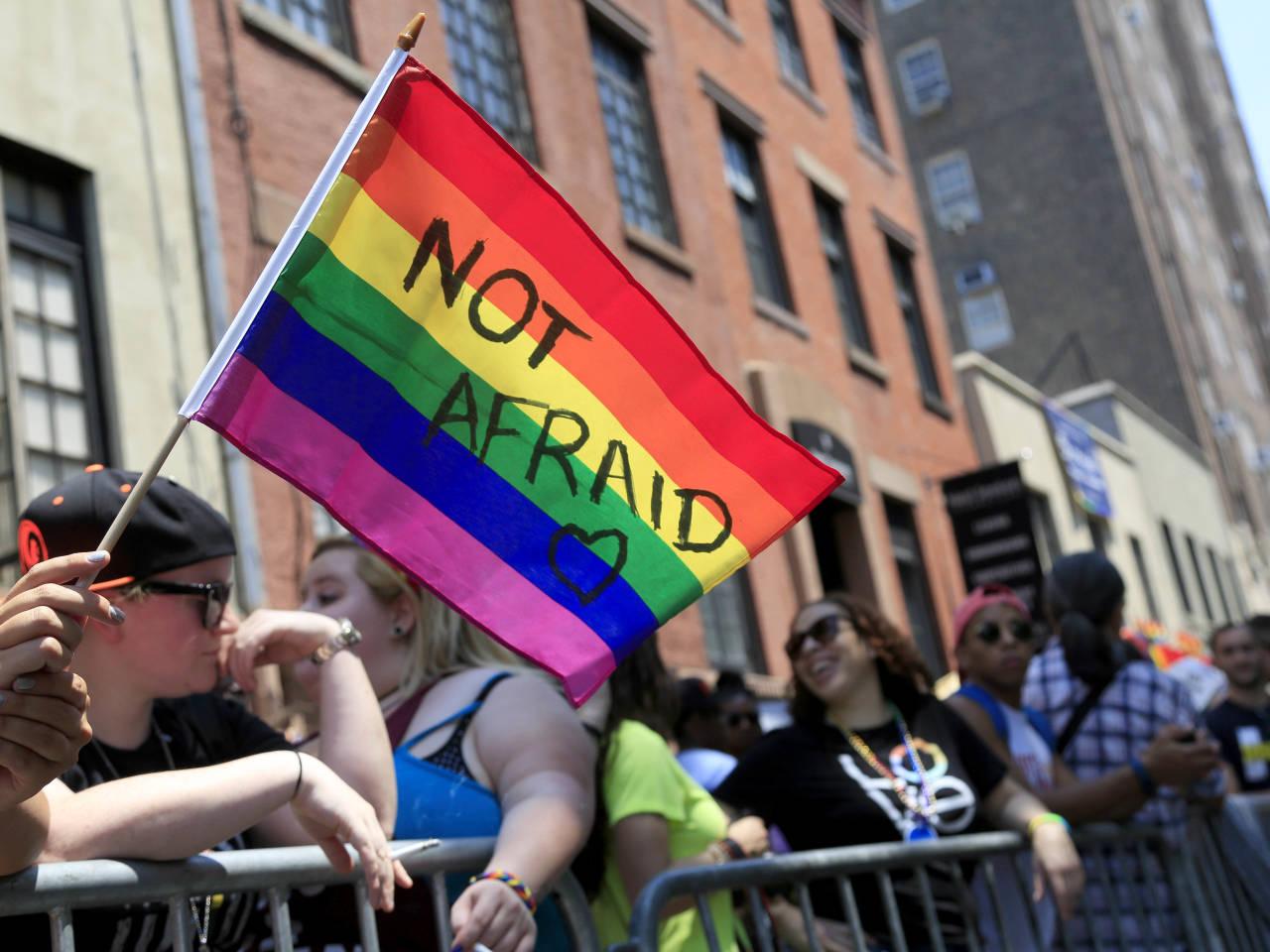 Tęczowa flaga w czasie demonstracjii z napisem NOT AFRAID
